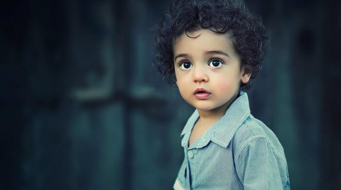 child with curly hair looking at the camera