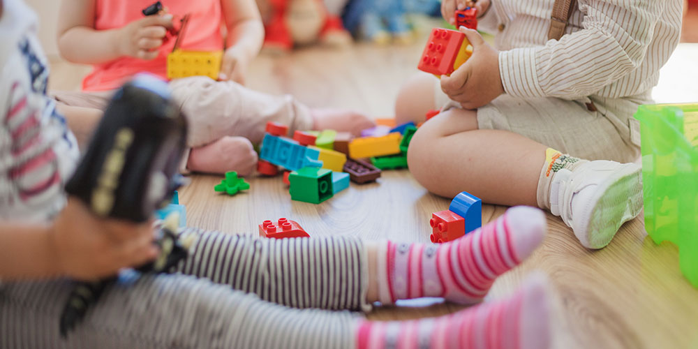 children playing with wooden toys on the floor