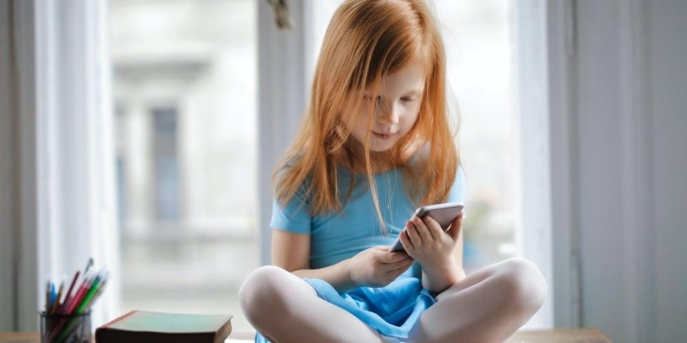 niña utilizando el teléfono redes sociales