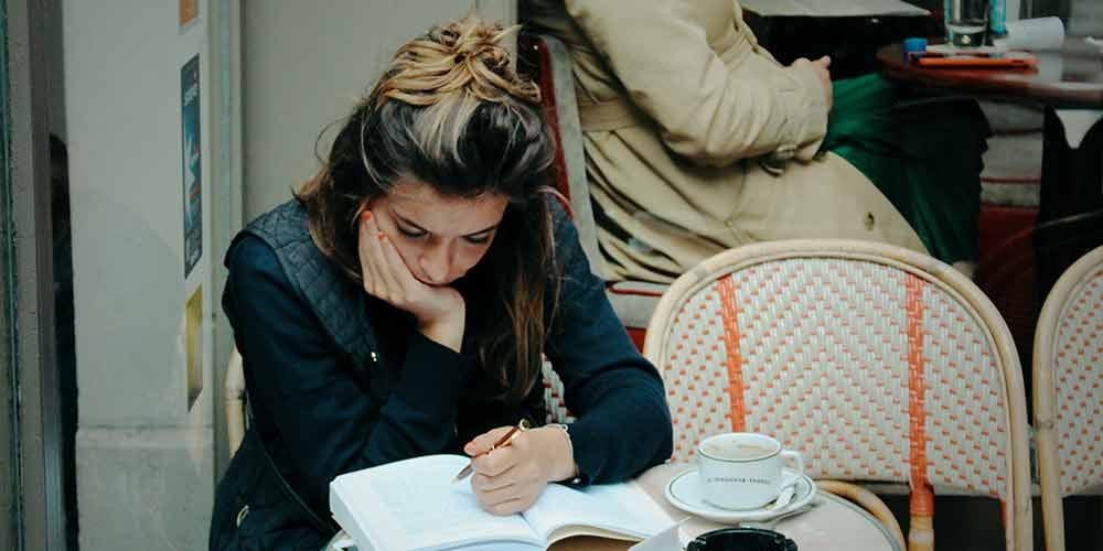 girl doing homework in a cafe