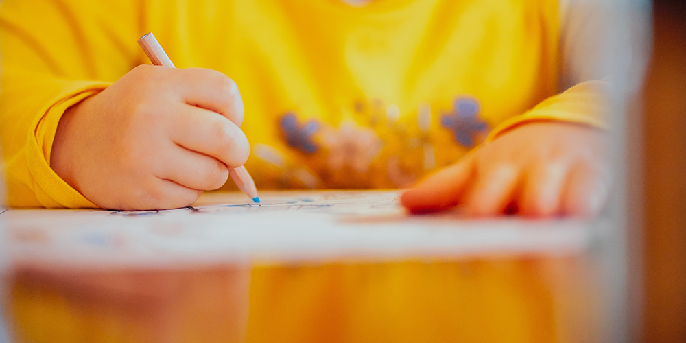 small boy in yellow jumper drawing a mind map
